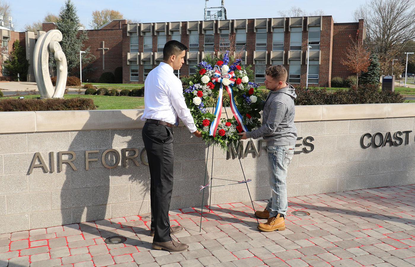 Luis Alvarado and Denis Connelly hanging a wreath on Veterans Day