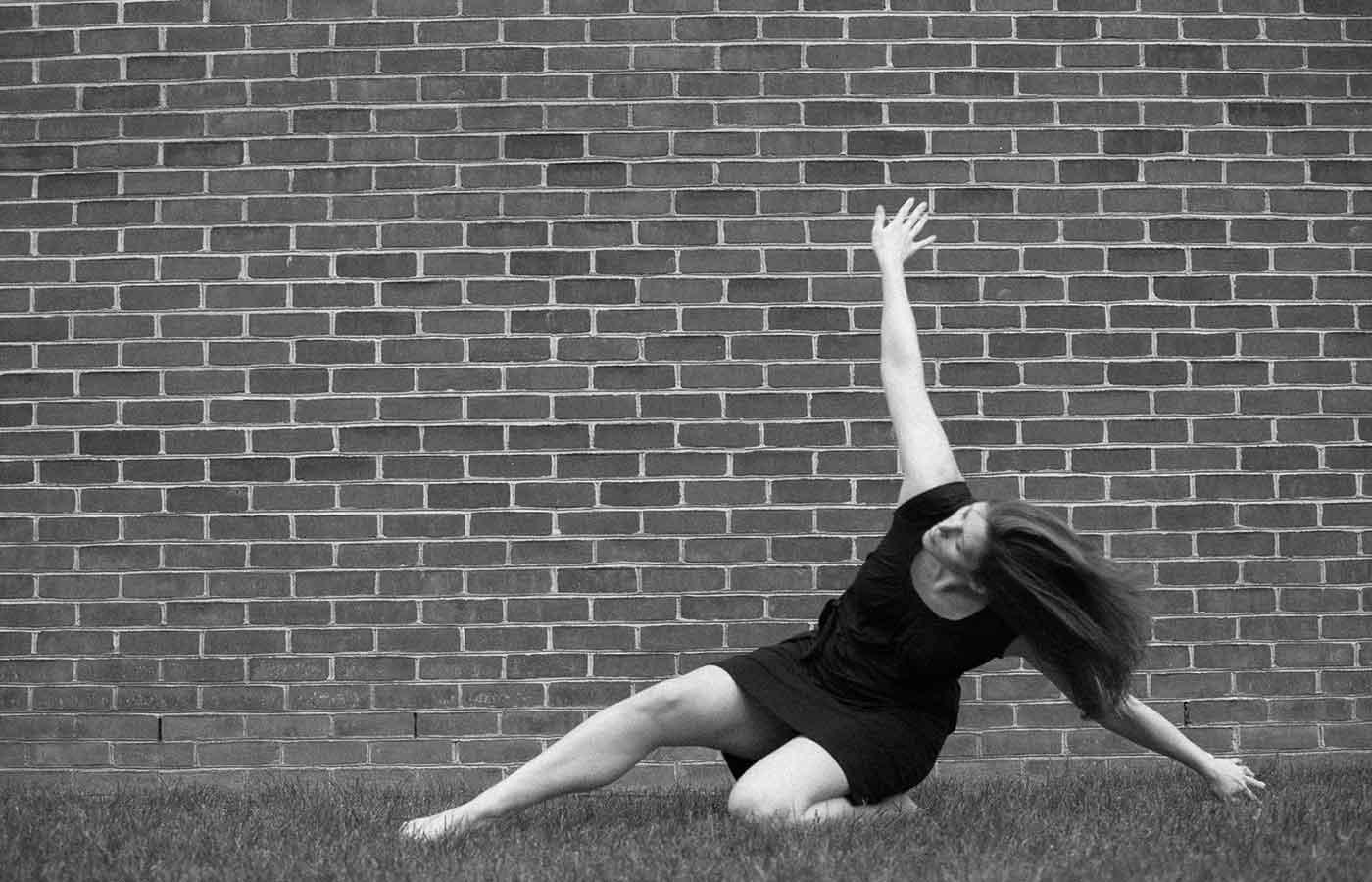 Angela Grossman dances in front of a brick wall - Marco-Calderon